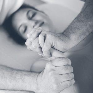 Physiotherapeut massiert die Hand einer Patientin